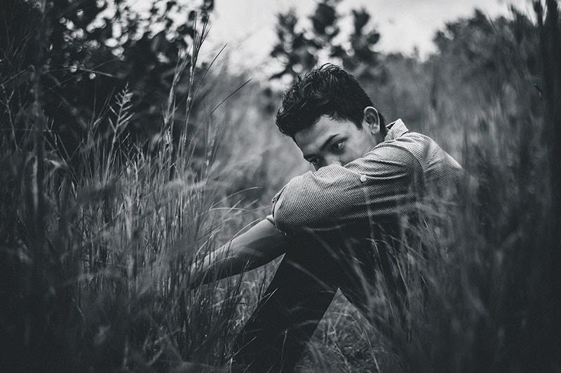 trauriger Mann, der auf dem Feld sitzt und weit weg schaut