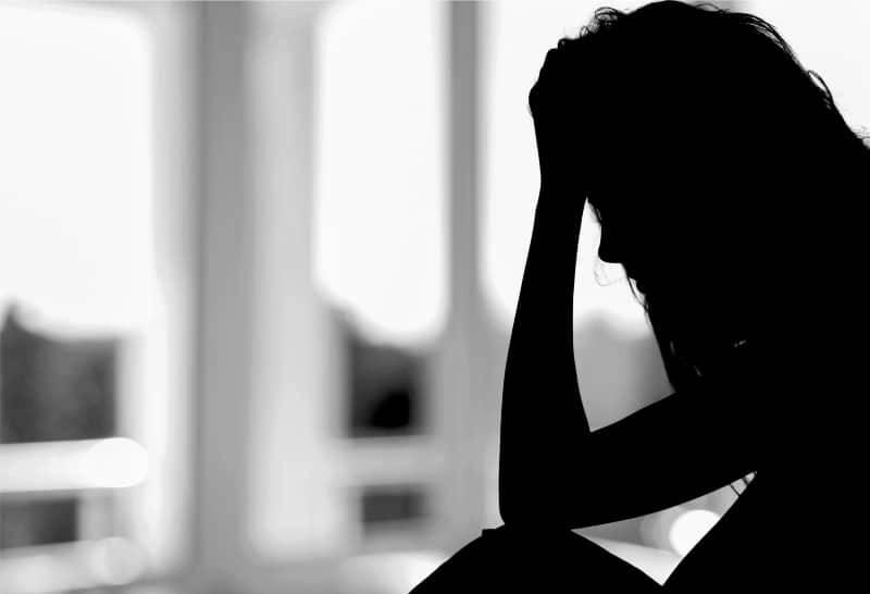 trauriges junges Mädchen, das im Dunkeln sitzt und weint