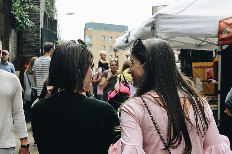 zwei Frauen gehen zusammen über den Straßenmarkt