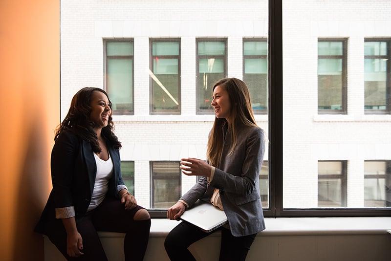 zwei Frauen lachen, während sie neben dem Fenster miteinander reden
