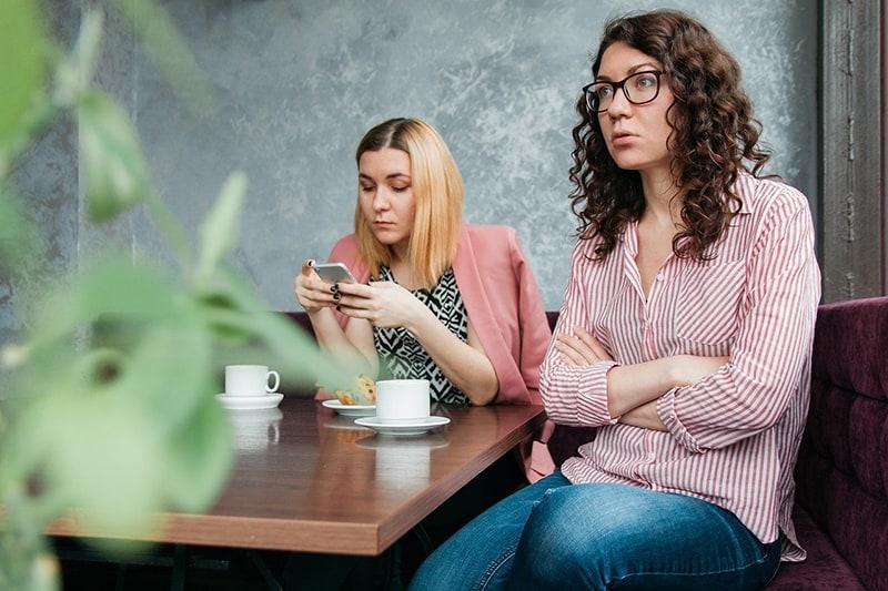 zwei Freundinnen sitzen zusammen ohne Kommunikation beim Treffen