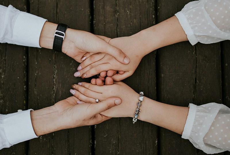 zwei Personen, die sich beim Abschied an den Händen halten
