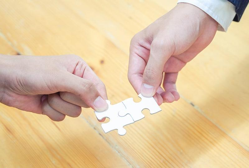 zwei Personen, die Teile eines Puzzles verbinden auf braun unter Holztisch