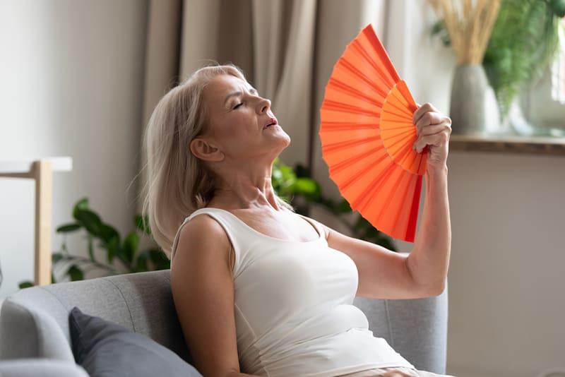 ältere Frau mit winkendem Fächer unter Überhitzung leiden