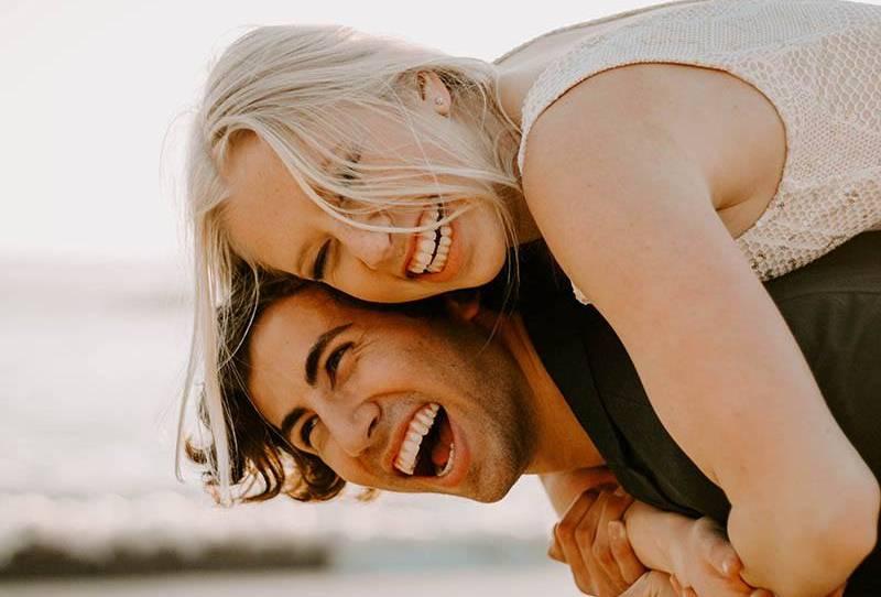 Nahaufnahme eines lächelnden Mannes, der draußen eine glückliche blonde Frau huckepack nimmt