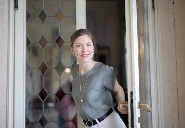 eine positive junge Frau, die durch eine Buntglastür eintritt