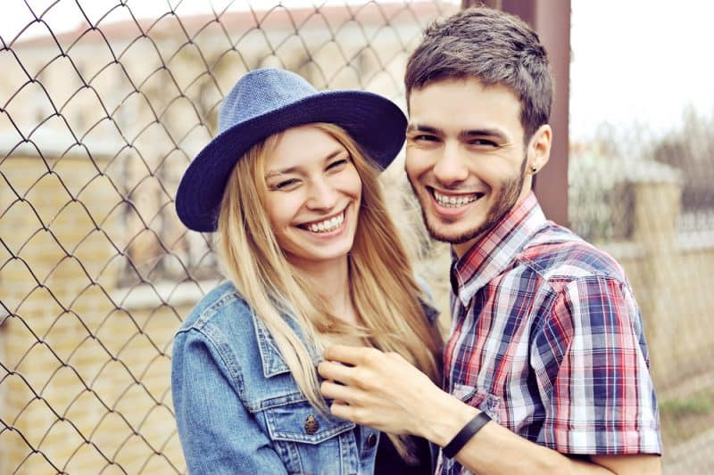 Eine schöne lächelnde Dame mit einem blauen Hut steht draußen neben ihrem glücklichen Mann