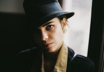 ein Porträt einer ernsthaften starken Frau mit einem Hut