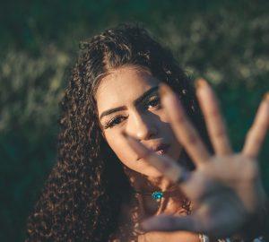 eine schöne Frau mit krausem Haar von traurigem Aussehen und erhobener Hand