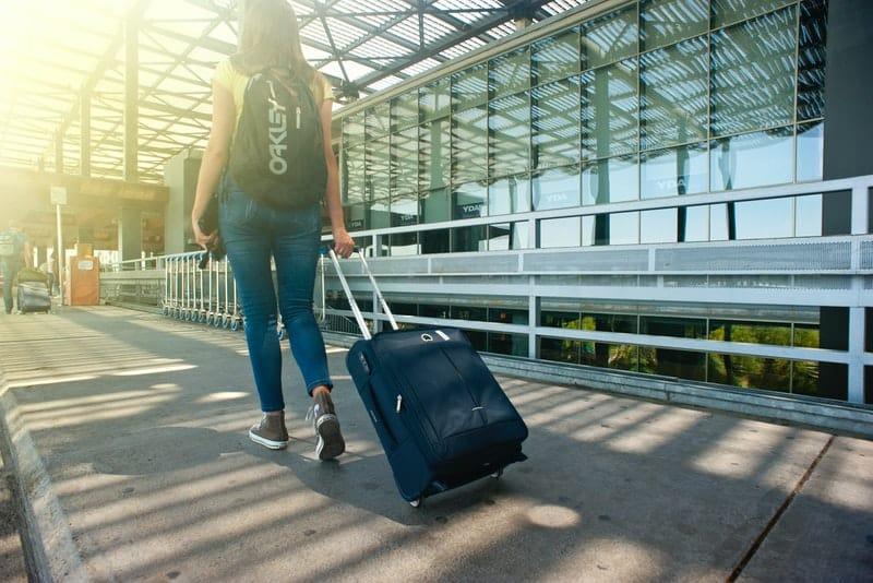 Das Mädchen mit Koffer und Rucksack geht irgendwohin