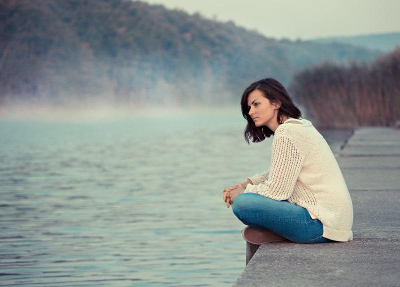 Das Mädchen sitzt in der Nähe des Sees