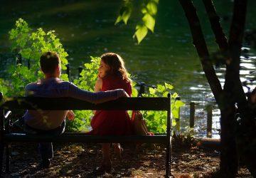 Ein Mann und eine Frau bei einem Date sitzen auf der Bank in der Nähe des Gewässers