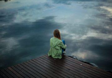 ein Mädchen sitzt am Ufer
