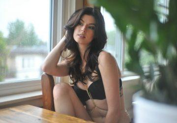 Eine Frau mit langen schwarzen Haaren sitzt in sexy Dessous