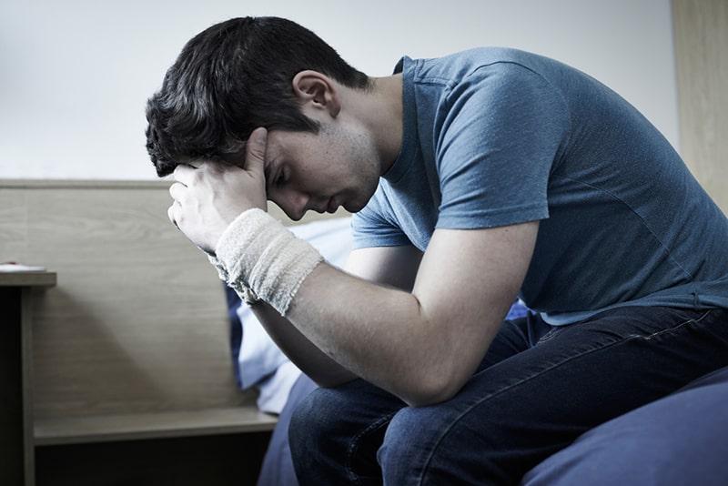 Depressiver junger Mann mit verbundenen Handgelenken nach Selbstverletzung auf der Couch sitzen
