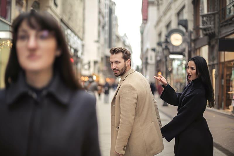 Der Mann dreht sich zu der Frau um, die neben ihm vorbeigeht, während er mit seinem Partner die Hände hält