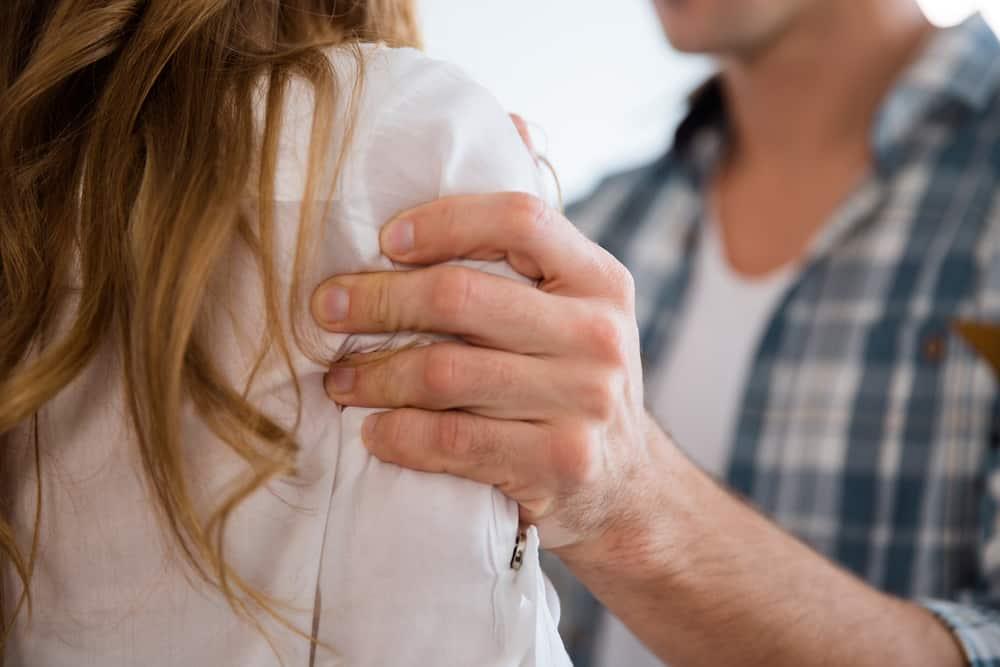 Der Mann hält die Frau grob und heftig an der Schulter