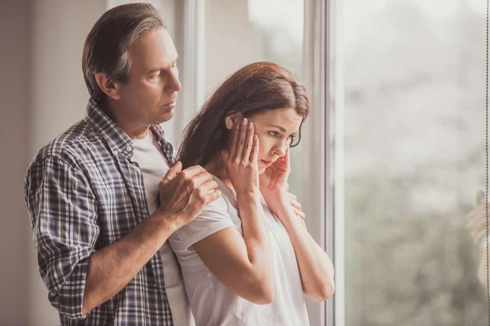 Der Mann im Hemd tröstet die traurige Frau