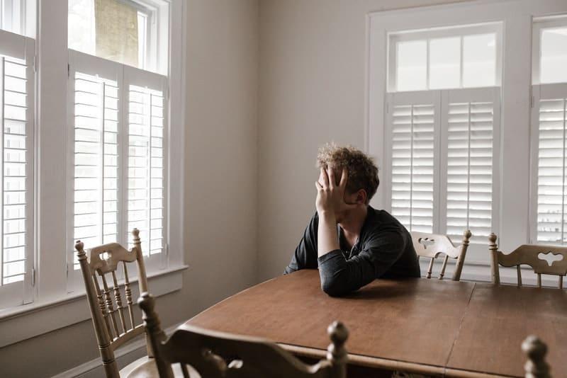 Der Mann sitzt am Esstisch und hält den Kopf