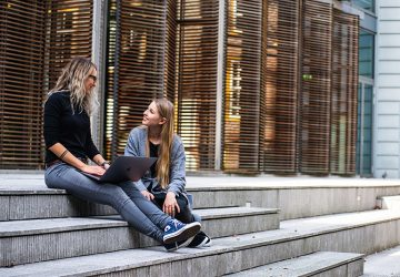 Zwei Frauen unterhalten sich auf der Treppe
