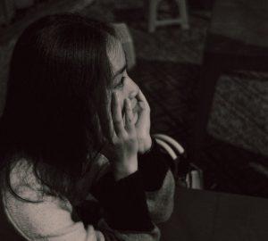 eine traurige Frau, die in einem dunklen Raum sitzt