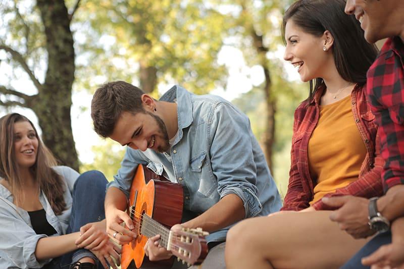 Ein Mann, der Gitarre spielt, während er mit Freunden sitzt