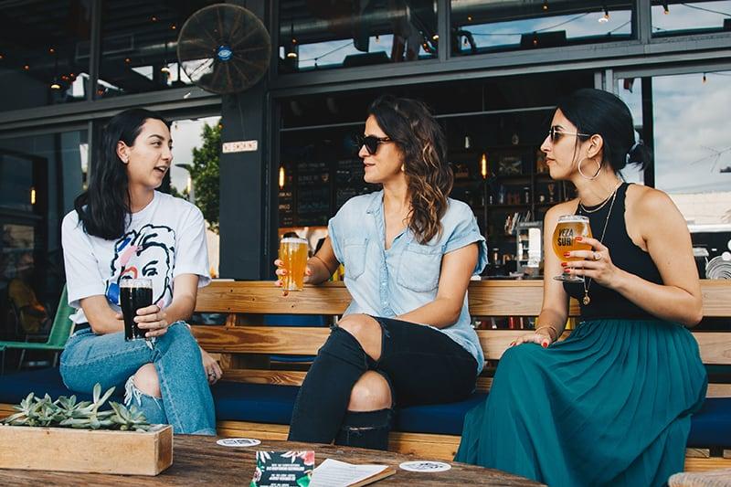 Drei Frauen trinken Bier, während sie zusammen sitzen