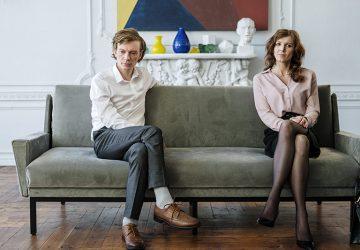 ein Ehepaar, das besorgt aussieht und auf der Couch sitzt