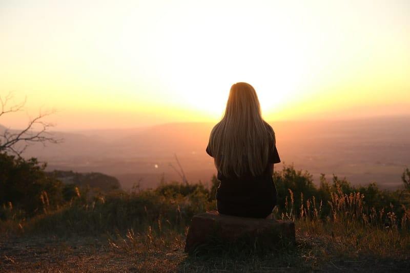 Ein Mädchen auf einem Hügel sitzt auf einem Felsen und beobachtet die Landschaft