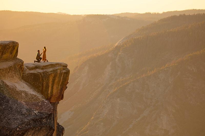 Ein Mann auf den Knien schlägt einer Frau auf einer Klippe in den Bergen vor