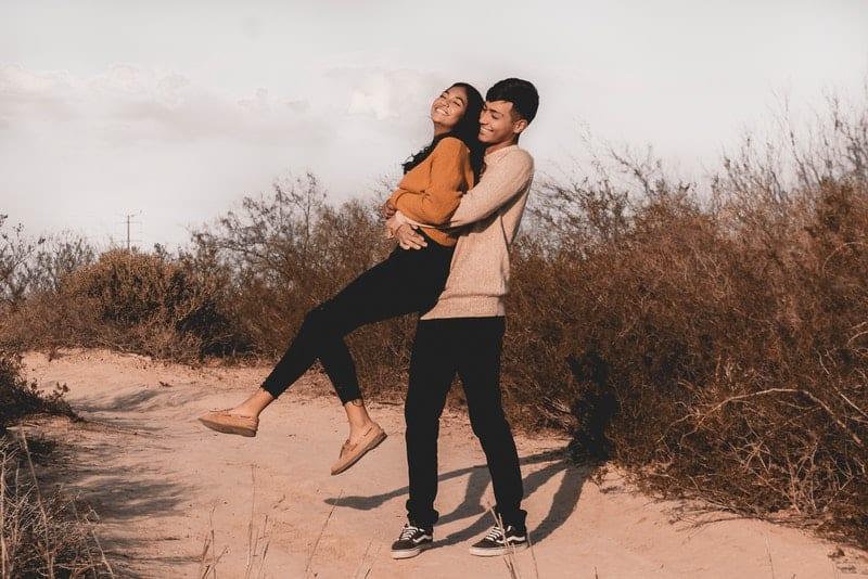 Ein Mann auf einem sandigen Weg hält seine Frau in den Armen