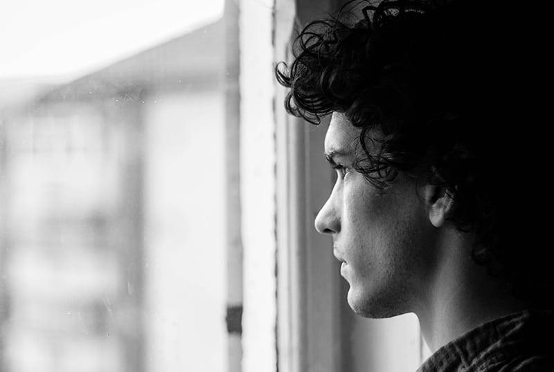 Ein Mann, der Angst hat, steht am Fenster und schaut durch das Fenster