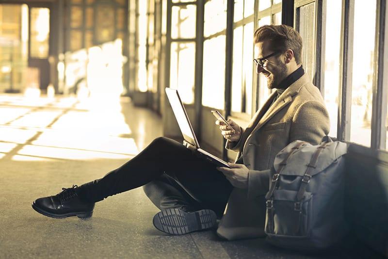Ein Mann, der Spaß daran hat, ein Smartphone zu benutzen, während er auf dem Boden der Station sitzt