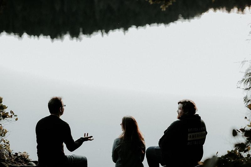 Ein Mann spricht mit Freunden, während er in der Nähe eines Gewässers sitzt