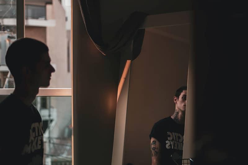 Ein Mann, der sich selbst ansieht, während er vor dem Spiegel im Raum steht