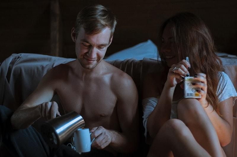 Ein Mann füllt die Tasse Kaffee neben einer Frau, die in einer intimen Atmosphäre Saft hält, während sie neben einem Bett sitzt