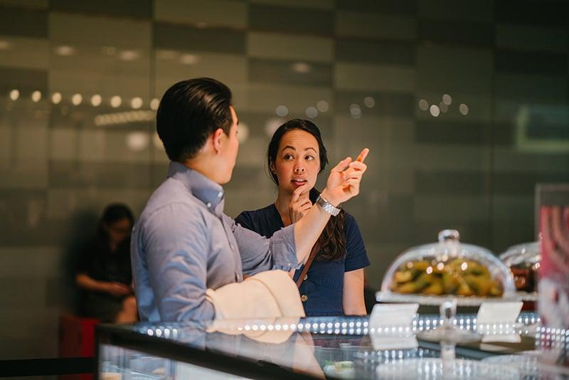Ein Mann gestikulierte mit der Hand, während er mit einer Frau in der Nähe der Bar sprach