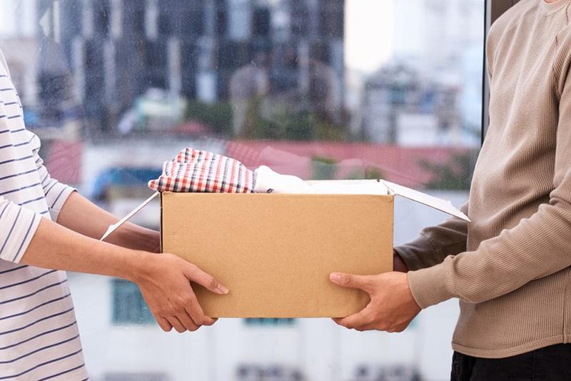 Ein Mann, der einer Frau Sachen in einem Karton zurückgibt