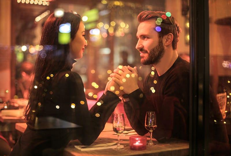 Ein Mann hält die Hand einer Frau, während er im Restaurant sitzt und Champagner trinkt