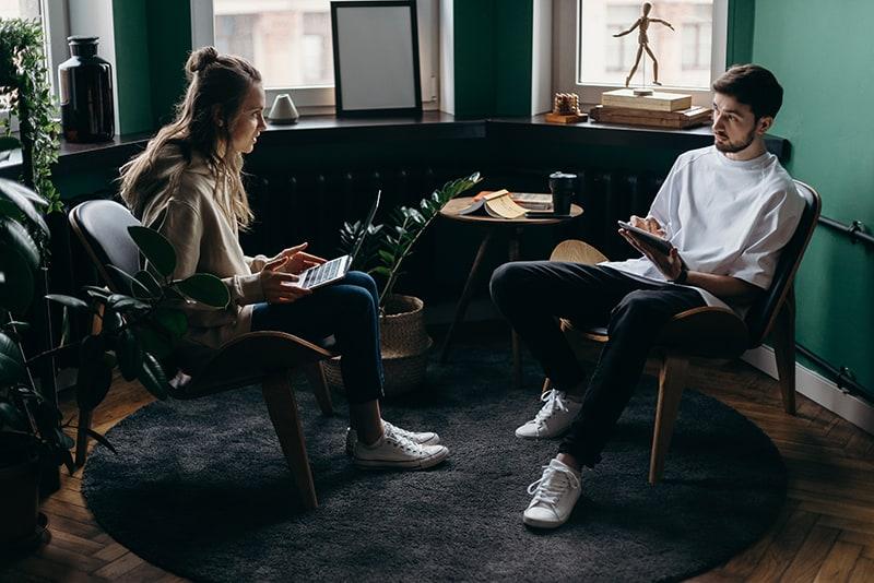 Ein Mann hört einer Frau zu, während sie auf den Stühlen im Raum sitzen