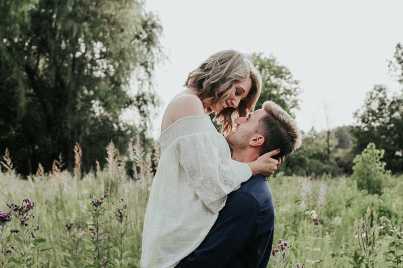 Ein Mann hebt eine Frau hoch, während er tagsüber auf einem Blumenfeld steht