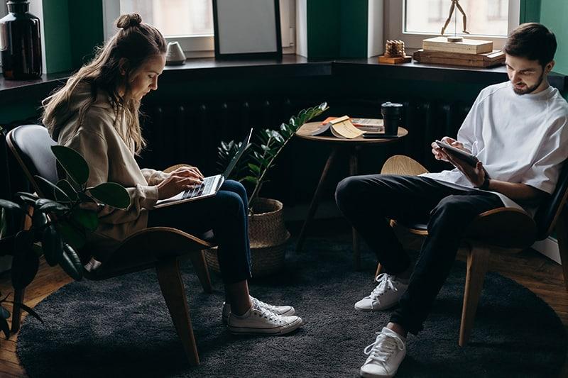 Ein Mann, der einer Frau hilft, ihren Job zu beenden, während er ein Tablet benutzt