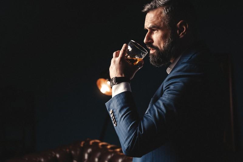 Ein Mann im Anzug schmeckt Wein
