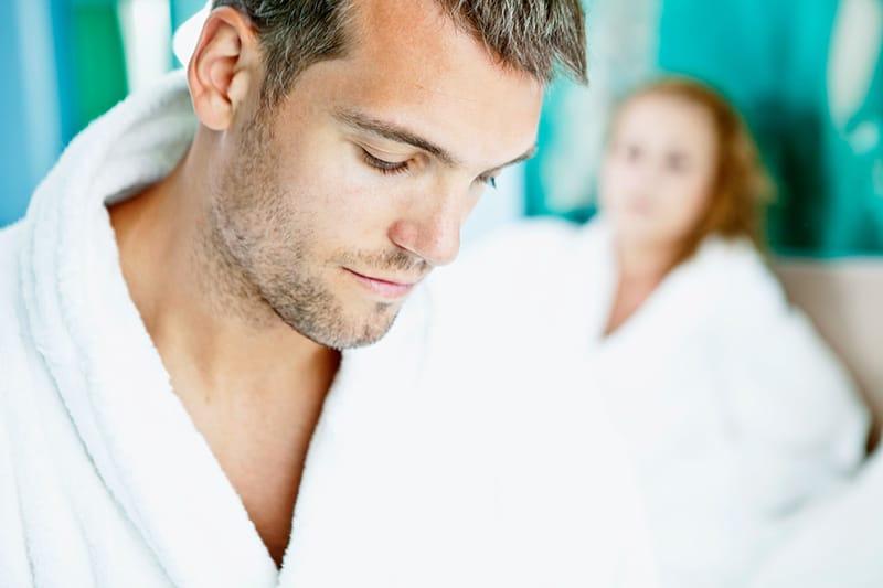 Ein Mann im Bademantel schaut nach unten, während er auf dem Bett in der Nähe einer Frau sitzt