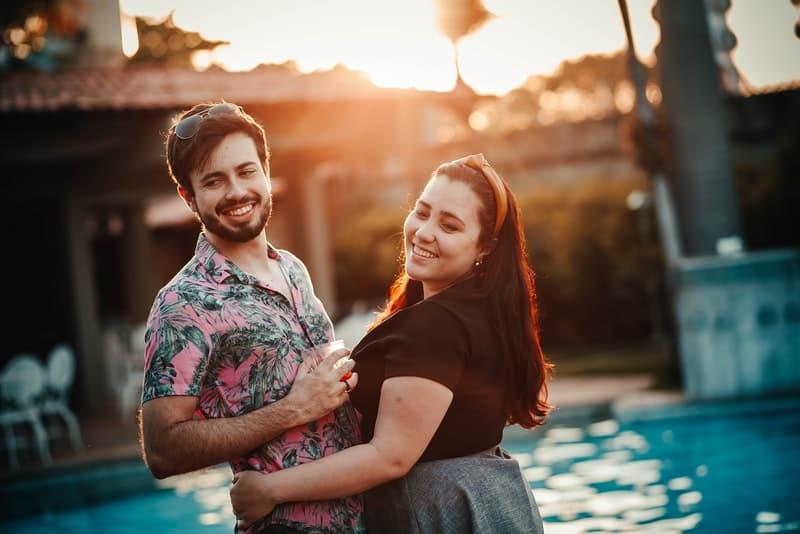 Ein Mann in einem Sommerhemd steht am Pool in den Armen einer dicken Frau