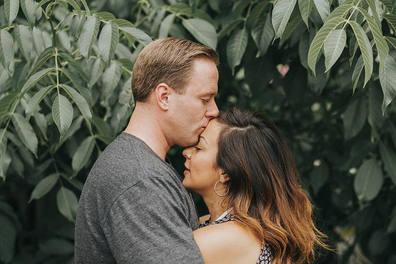 Ein Mann küsst eine Frau auf die Stirn, während er sich in der Nähe von grünen Pflanzen umarmt