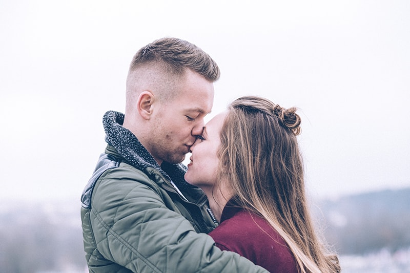 Ein Mann küsst eine Frau auf die Stirn, während er sie tagsüber draußen umarmt