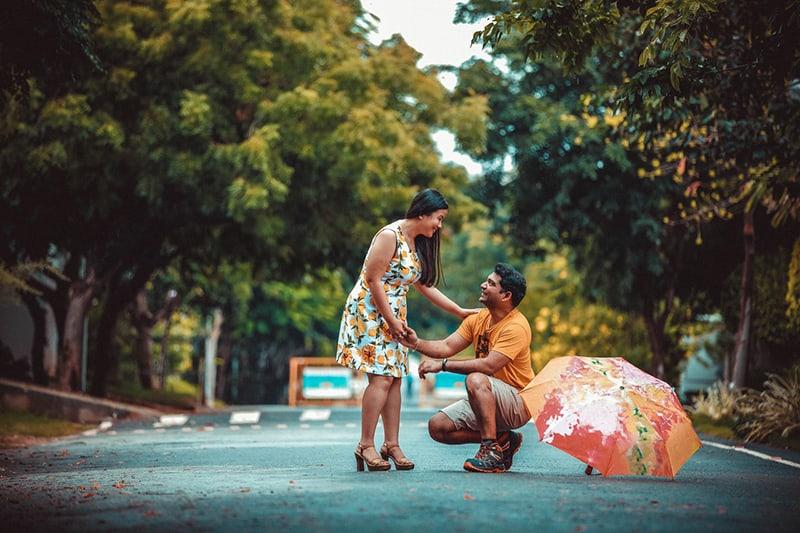 ein Mann kniet vor einer Frau neben einem Regenschirm auf der Straße