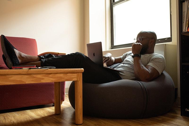 Ein Mann legt seine Beine auf den Couchtisch, während er einen Laptop benutzt