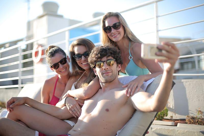 Ein Mann macht ein Selfie, umgeben von drei Freundinnen im Schwimmbad